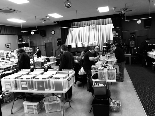 Stalls at a record fair with people milling around and crate-digging
